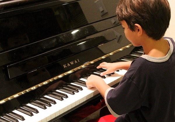 маленький музыкант играет на пианино